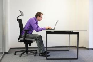 20067343 - bad sitting posture at laptop . man on chair