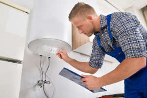 44591897 - male worker with clipboard adjusting temperature of water heater