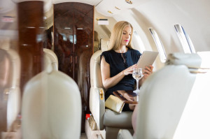 Woman Using Tablet Computer In Private Jet
